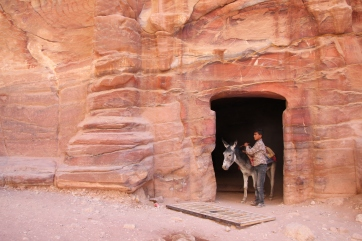 A boy and his donkey exit a cave